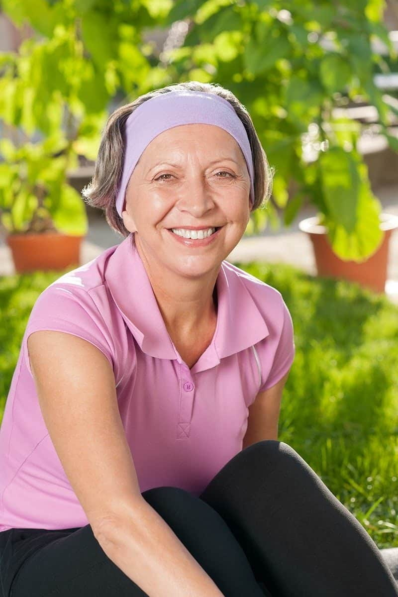 Older woman smiling with trees behind her about alternative cancer treatments