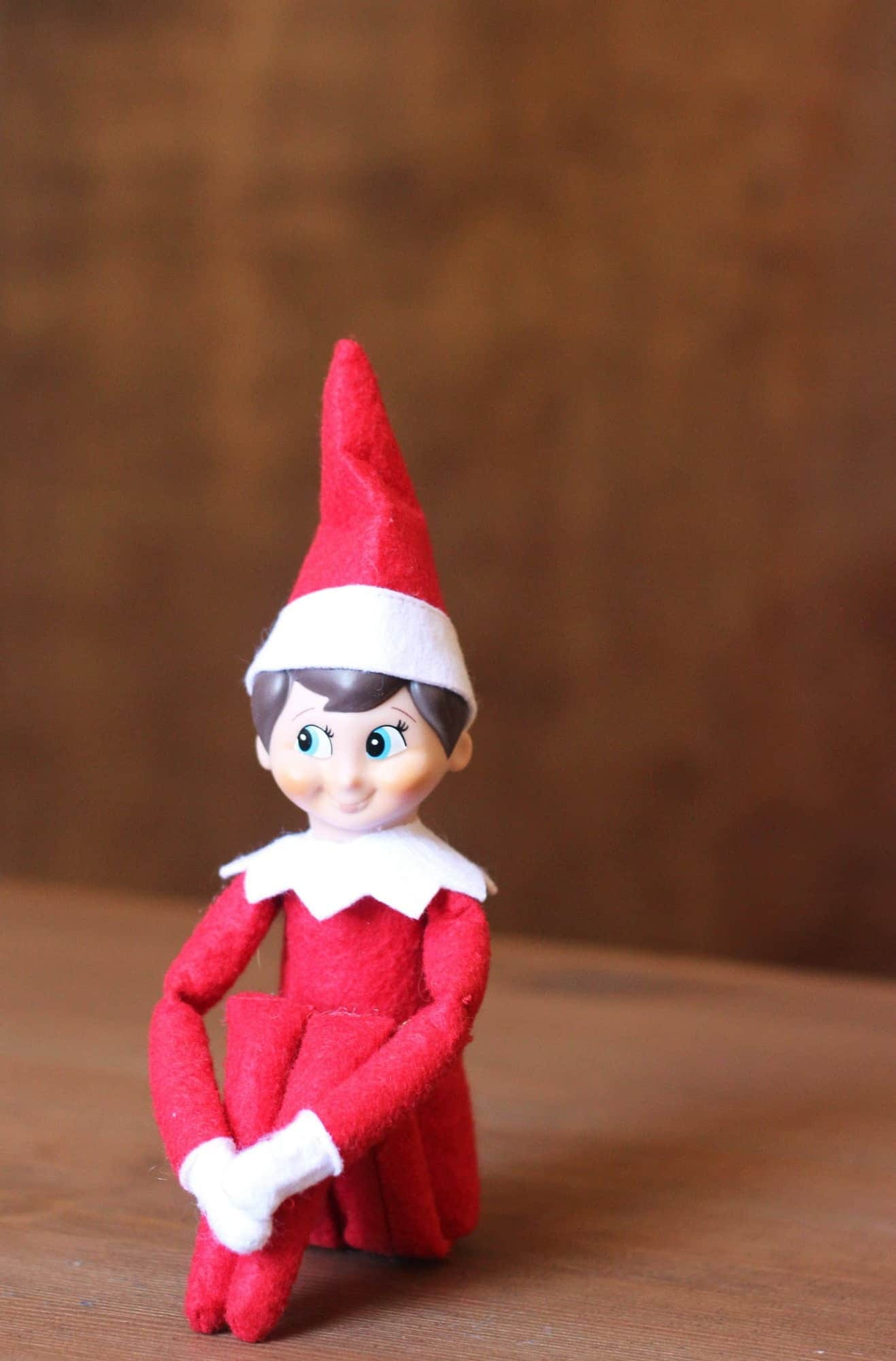 Elf on the shelf sitting on a brown table with a brown background.