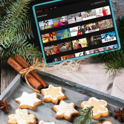 A tray of cookies with a tablet with an array of good Christmas movies on Netflix on the screen.