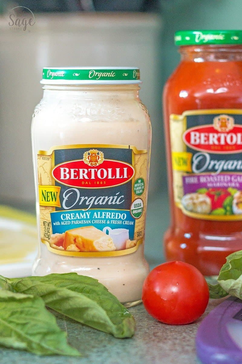 jar of Bertolli Organic creamy alfredo sauce on a counter with fresh basil