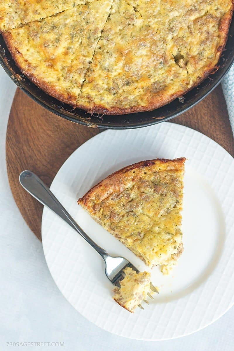 overhead shot of a breakfast quiche on a white plate with a fork