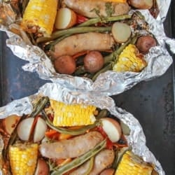 hobo dinner sausage and veggies in foil on a sheet pan