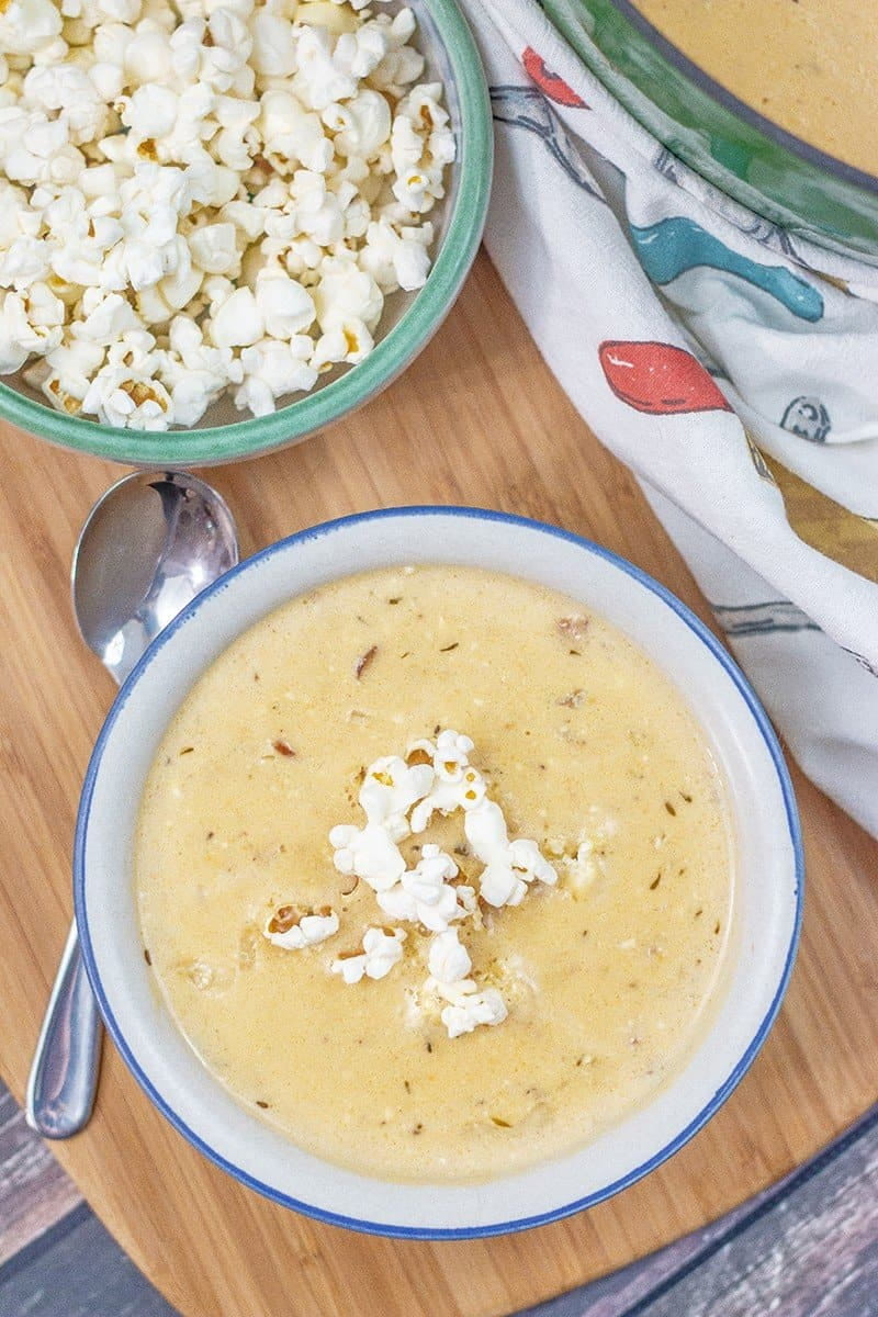 beer cheese soup in a white and blue bowl on a wooden board