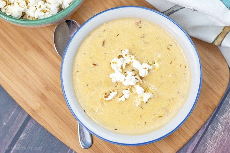 low carb beer cheese soup in a white and blue bowl on a wooden board
