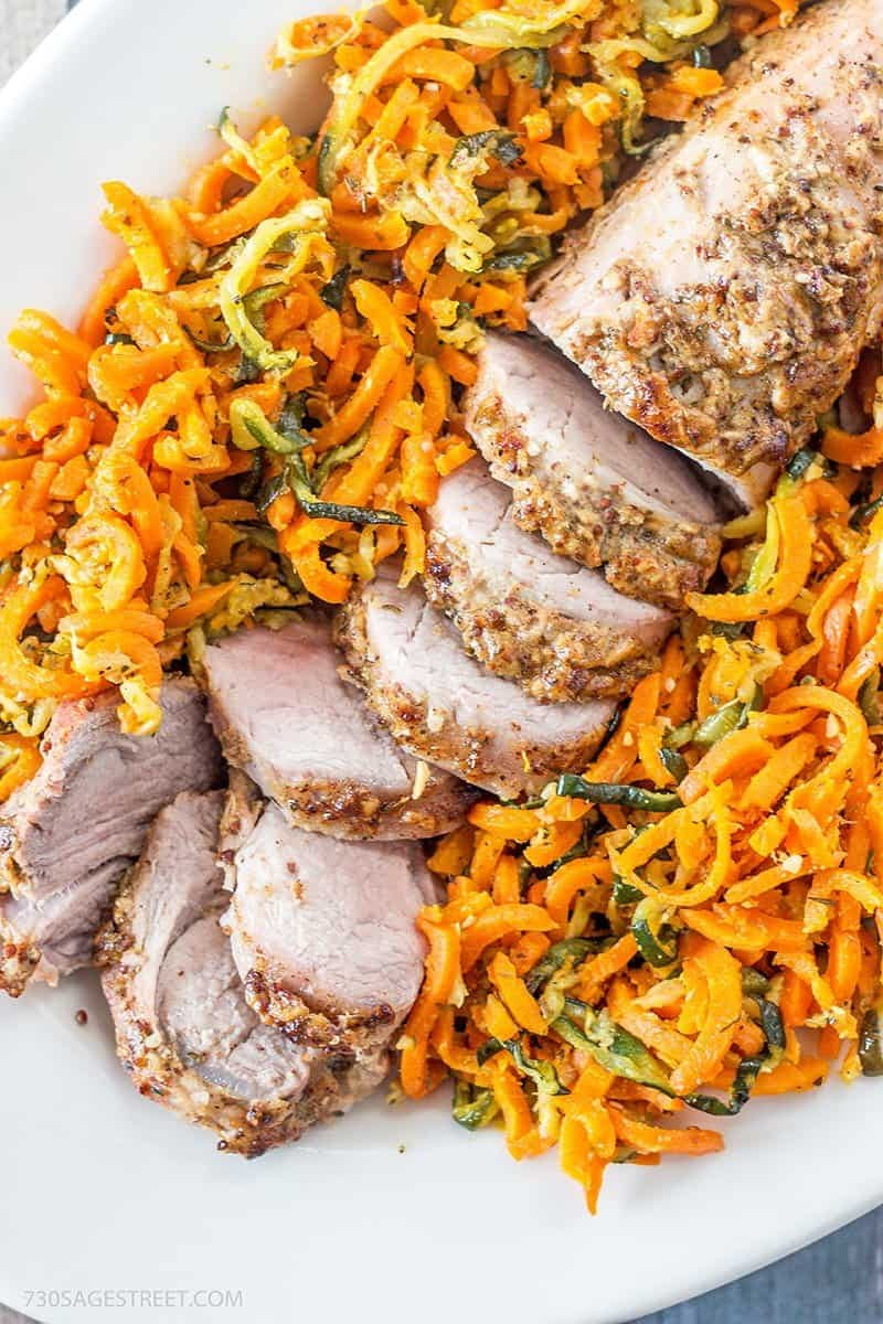 white plate with a sliced pork tenderloin nestled in a bed of spiral carrots and zucchini