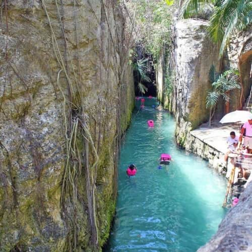 underground river between two large limestone walls with people in pink life vests swimming away