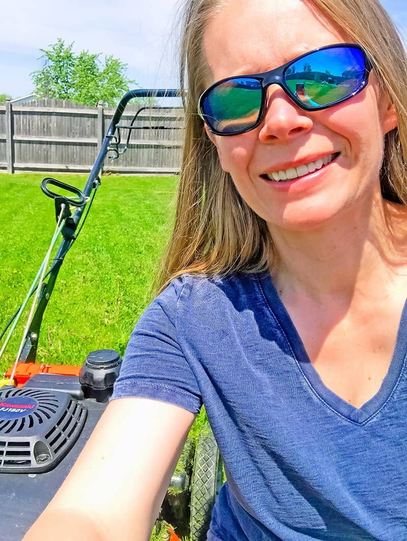 woman in front of a lawn mower