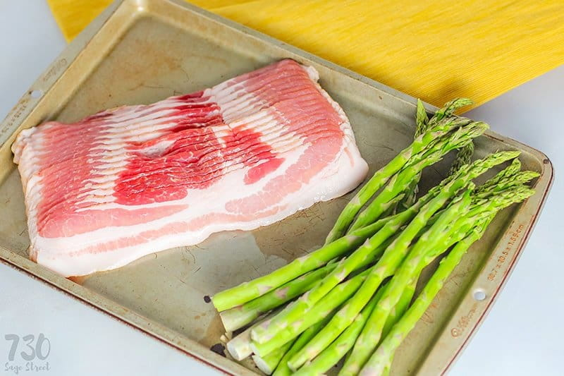 raw bacon and fresh asparagus on a cookie sheet