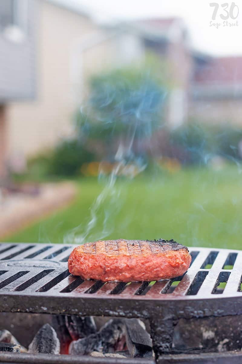 The Beyond Burger cooking on a grill with smoke