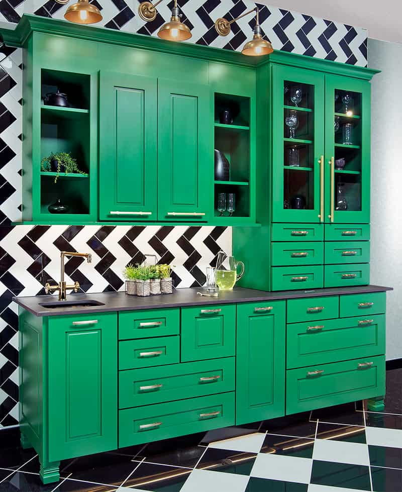 green frameless cabinets with a black and white wall behind them