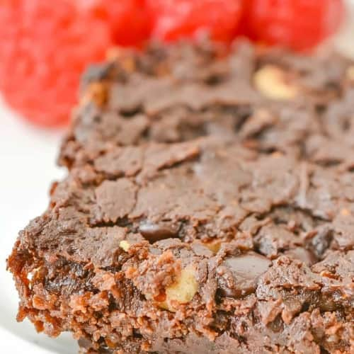 keto brownies on a white plate in front of raspberries