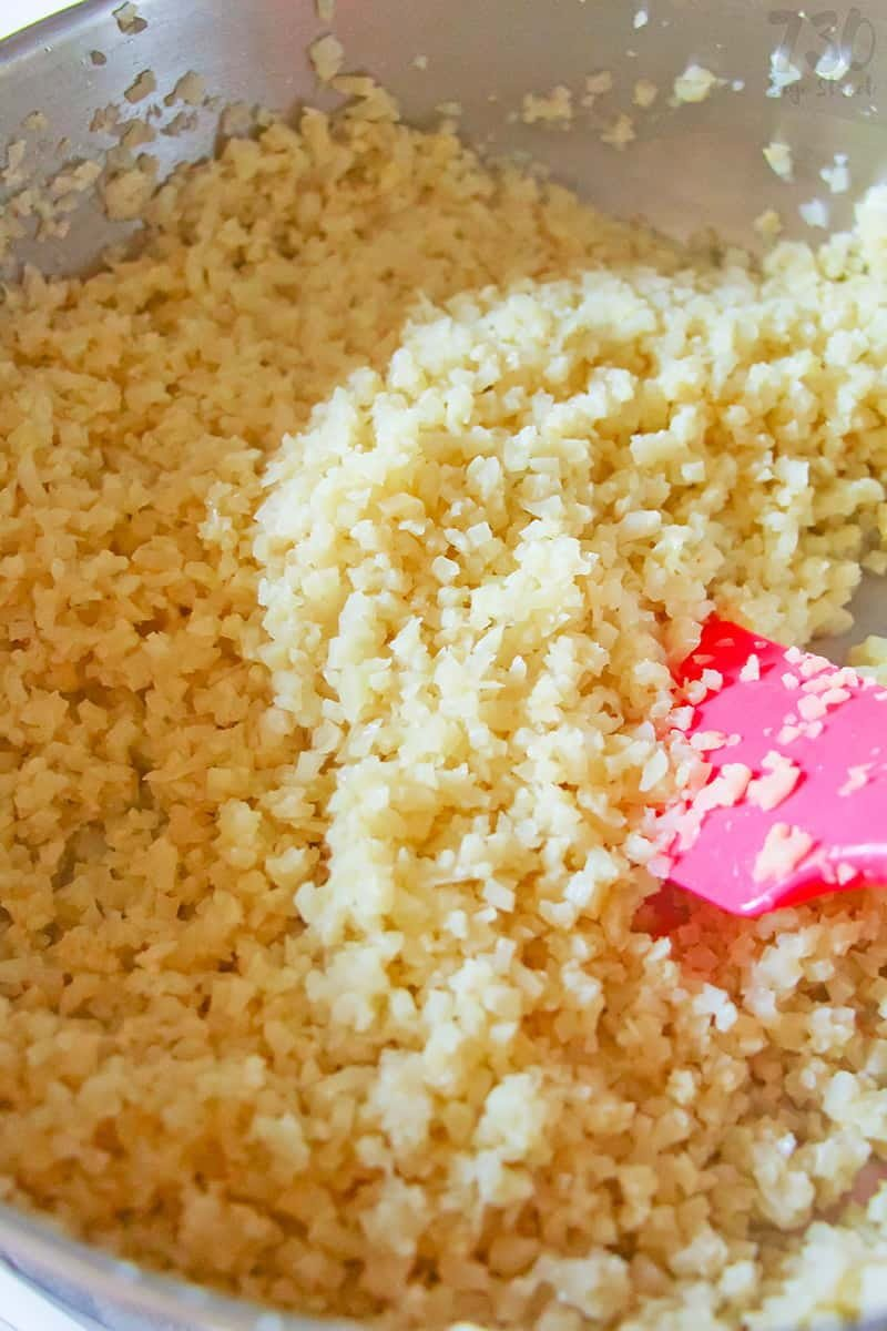 riced cauliflower being mixed in a bowl
