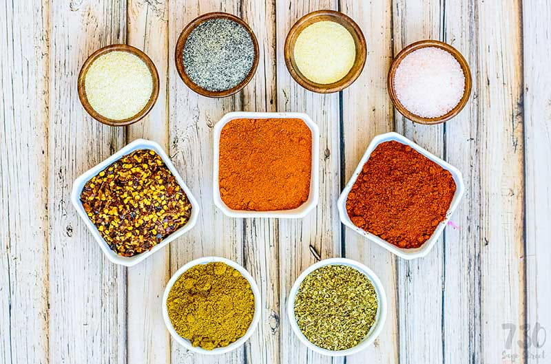 Mexican spices in bowls for taco seasoning on a wood background