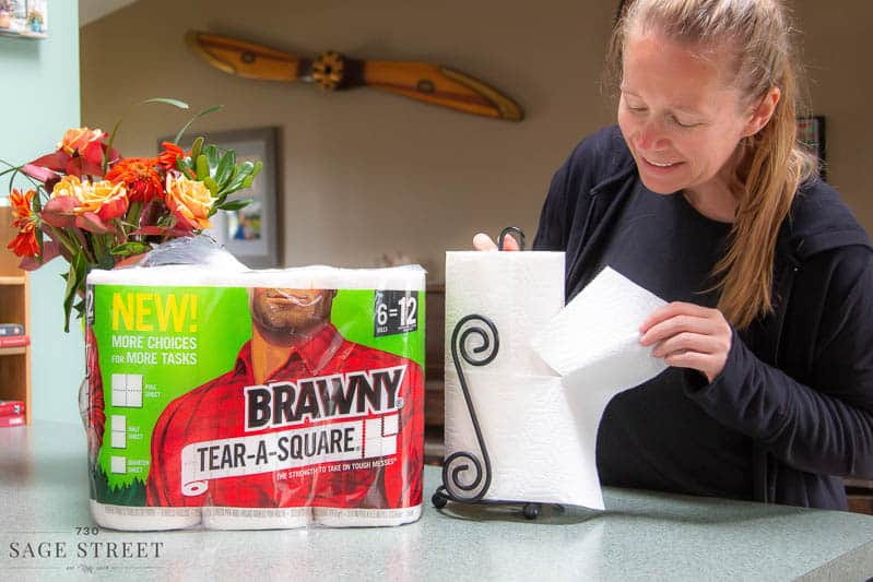 woman tearing a quarter sheet of paper towel off a roll of Brawny Tear-A-Square paper towels.