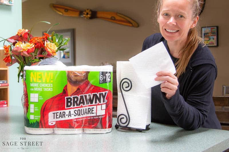 smiling woman tearing a quarter sheet of paper towel off a roll of Brawny Tear-A-Square paper towels.