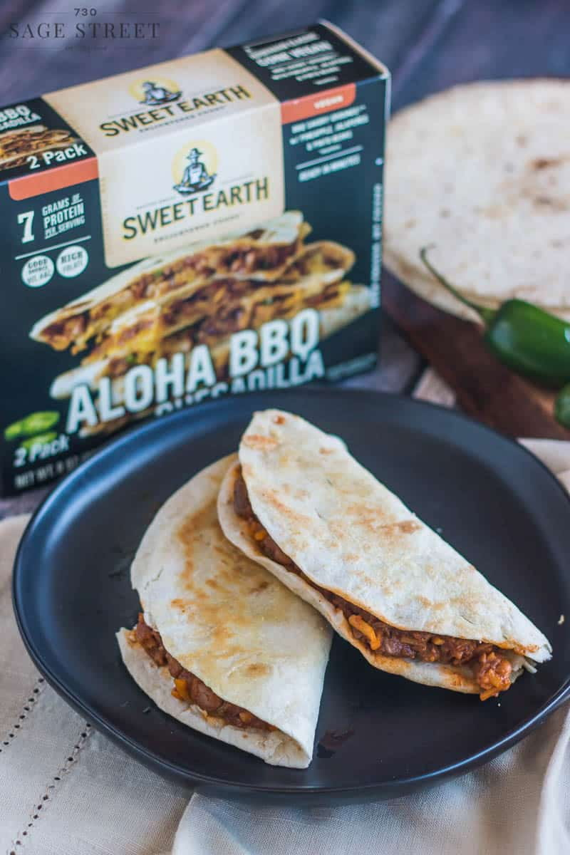 Sweet Earth Foods Aloha BBQ quesadilla on a black plate next to the product packaging