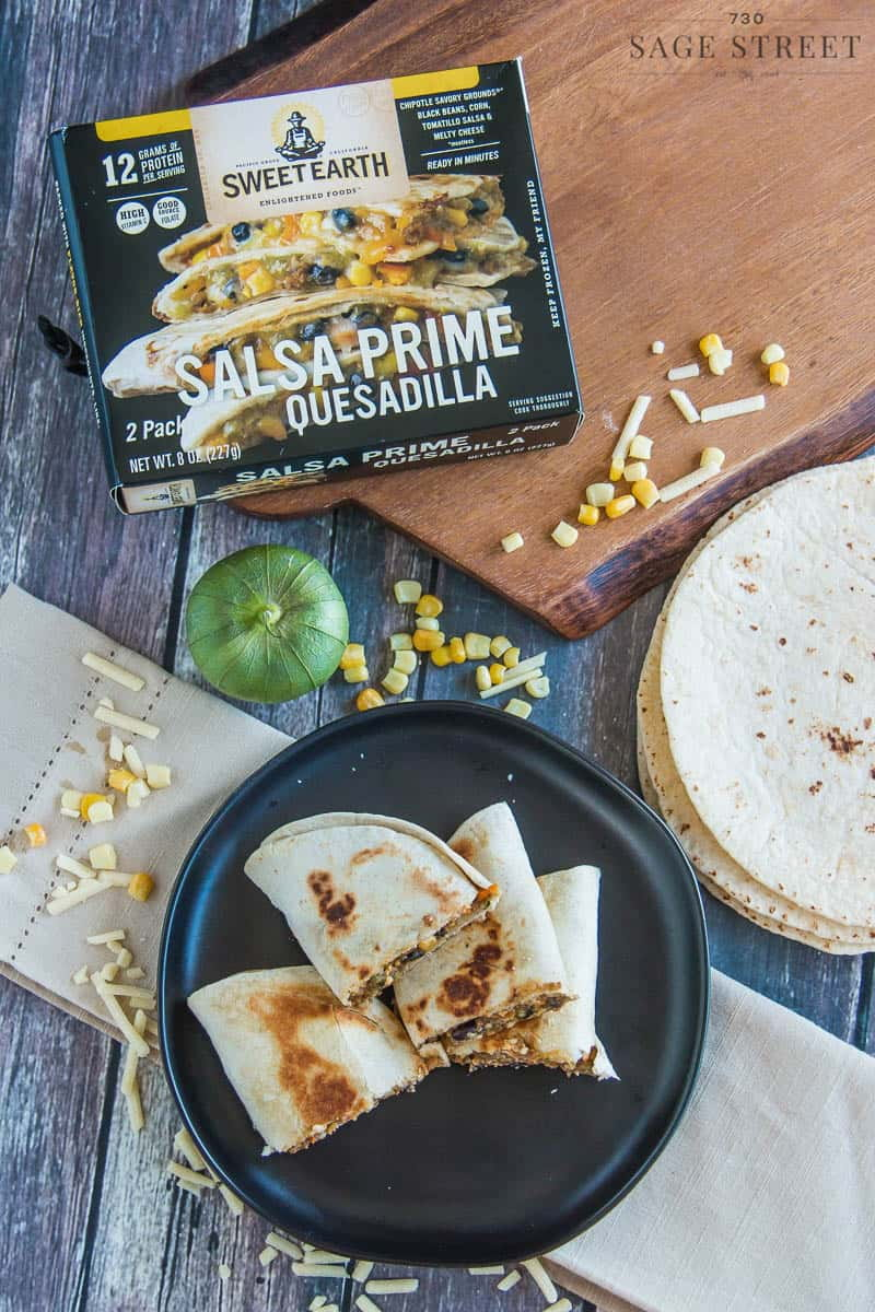 Sweet Earth Foods salsa prime quesadilla on a black plate next to the product packaging