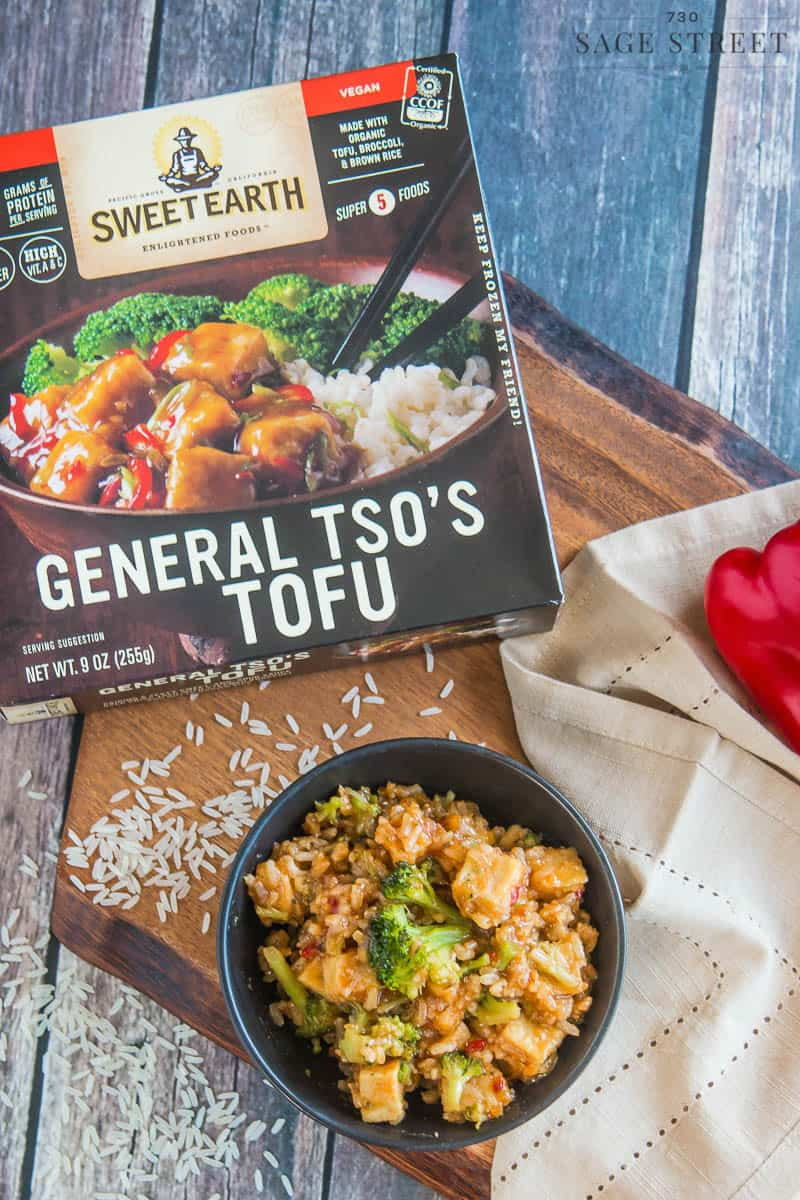 Sweet Earth Foods General TSO's Tofu in a black bowl with the product packaging next to it.