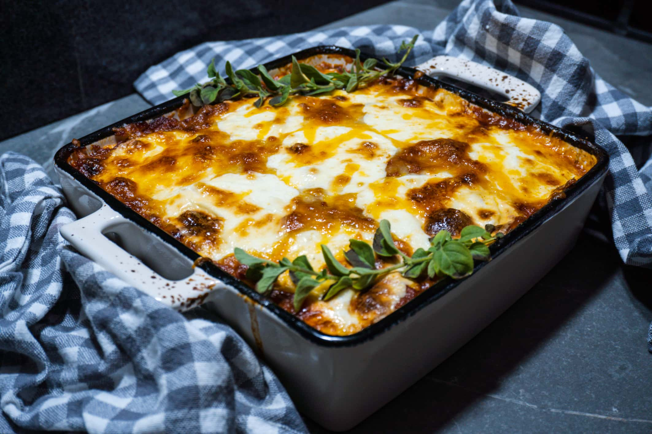 Out of the oven this delicious Keto Lasagna in white and blue stoneware baking dish.