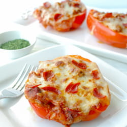 Pizza Stuffed Red Bell Peppers on white plate with fork.