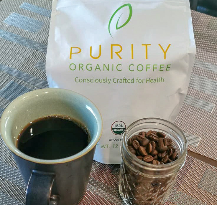 Vintage Black Coffee mug with freshly brewed Purity Coffee (left). Purity Coffee bag (center), and small jar with purity coffee beans (right)