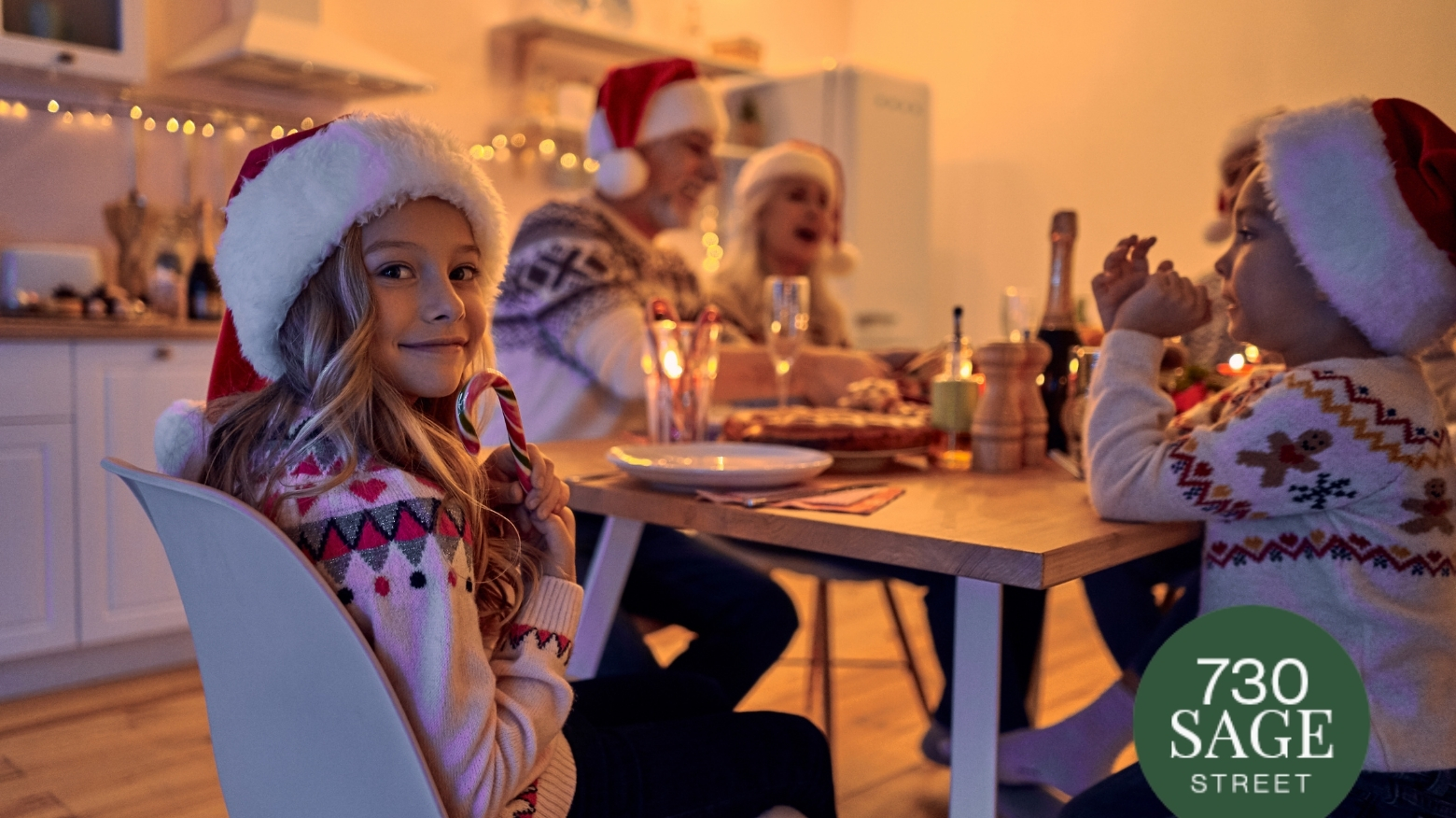 Girl smiling, sitting at dinner table, wearing Christmas clothes and excited to eat Xmas Dinner.
